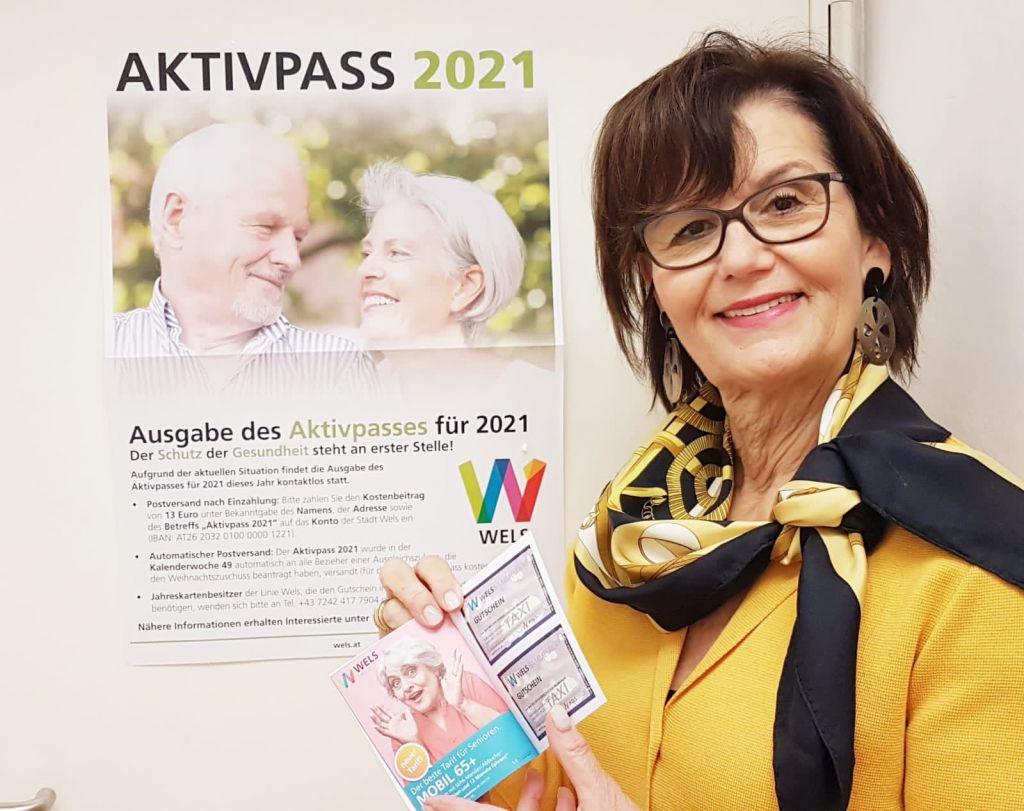 Stadträtin lächelt in Kamera mit dem aktuellen Aktivpass-Heft für das Jahr 2021. Im Hintergrund ein Plakat mit Richtlinien zur Ausgabe