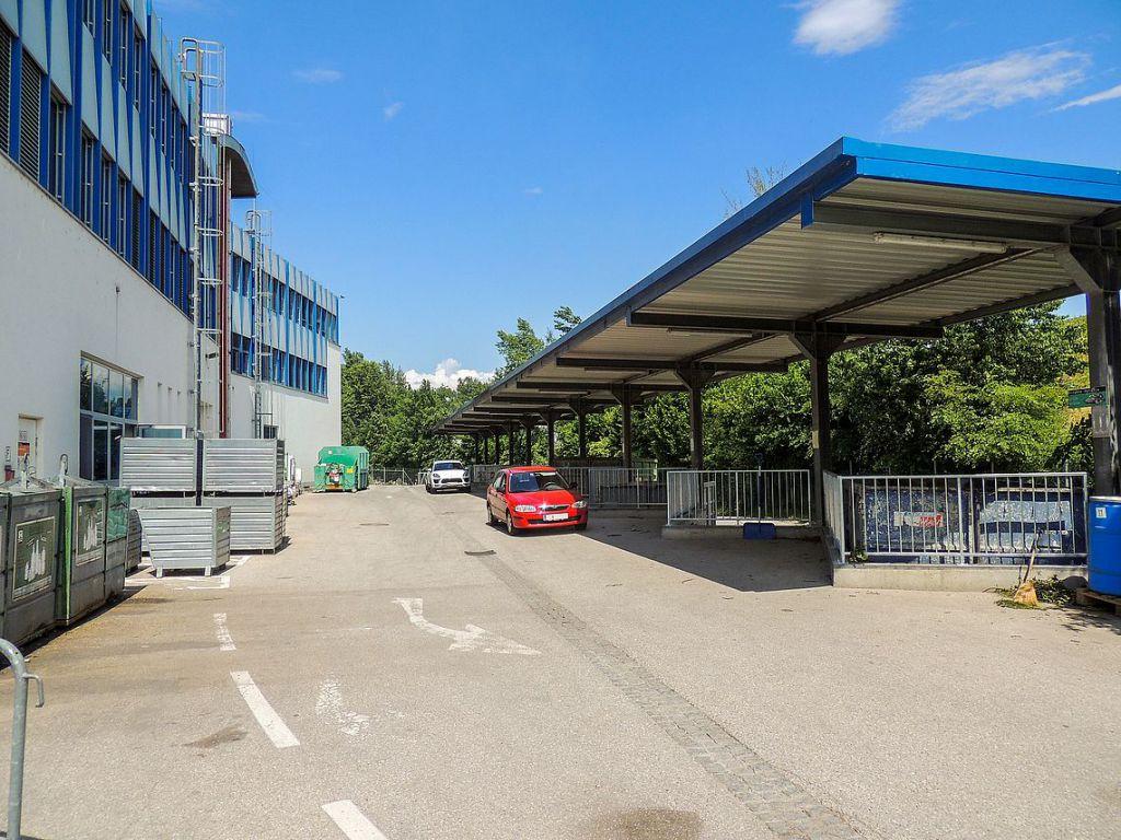 rotes Auto auf einem Altstoffsammelhof vor den Containern