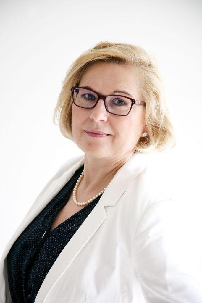 freundliche Frau, im mittleren Alter, mit blonder Bob-Frisur und Brille trägt weißen Blazer mit schwarzer Bluse und Perlenschmuck