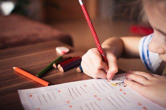Kind schreibt etwas auf ein Papier
