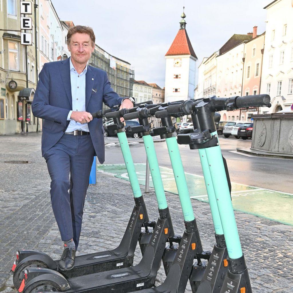 Vizebürgermeister Gerhard Kroiß steht hinter einer Gruppe von E-Scootern auf dem Stadtplatz, im Hintergrund ist der Ledererturm zu sehen