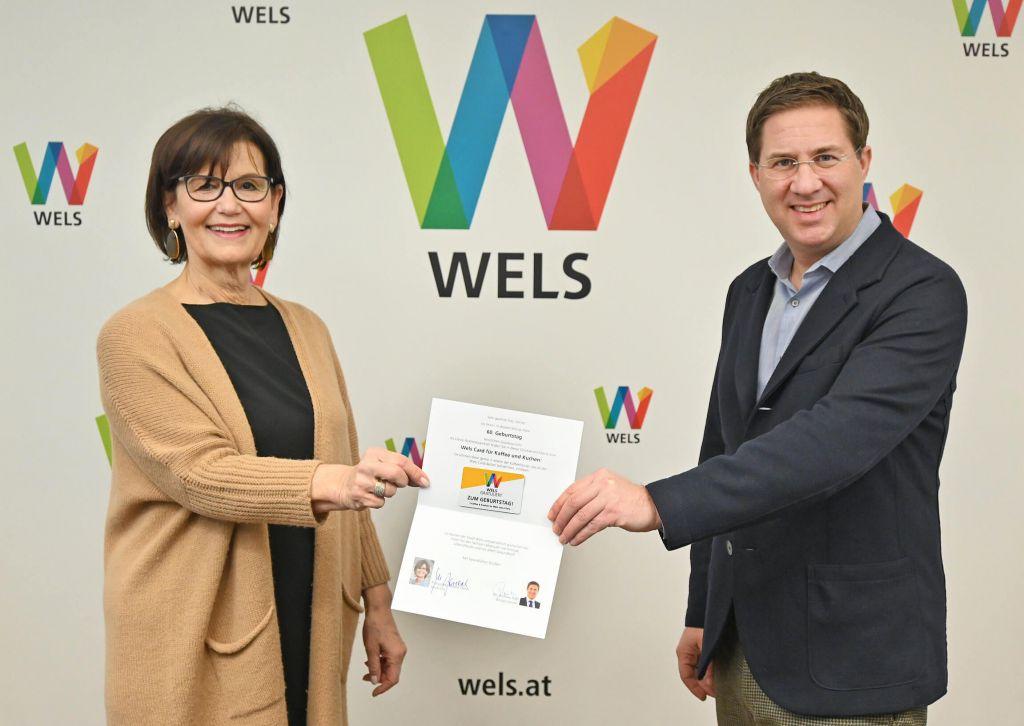 Bürgermeister Dr. Rabl und Stadträtin Josseck-Herdt, Referentin für Generationen, halten gemeinsam mit Abstand eine Geburtstagskarte mit der Wels-Card
