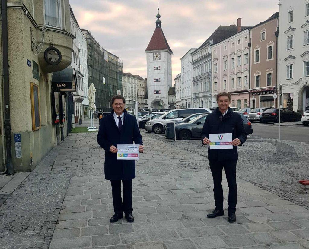 Bürgermeister Rabl und Vizebürgermeister Kroiß stehen mit den Förderungsschilderung auf dem Stadtplatz