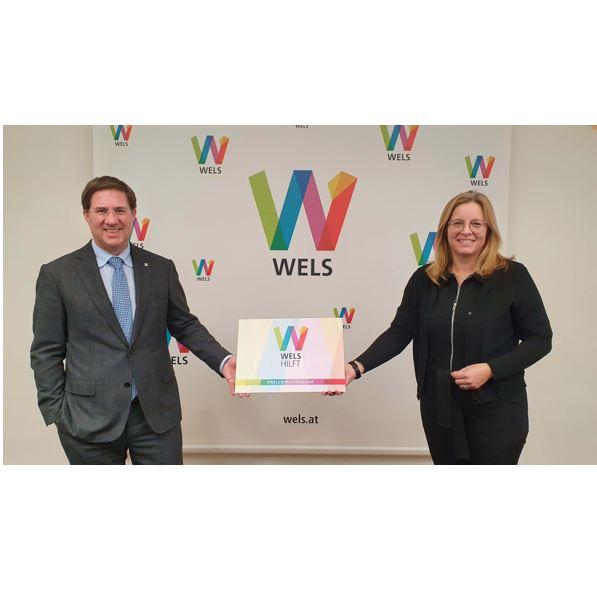 Bürgermeister Dr. Andreas Rabl und Vizebürgermeisterin und Sozialreferentin Christa Raggl-Mühlberger halten ein Schild mit der Aufschrift: Wels hilft
