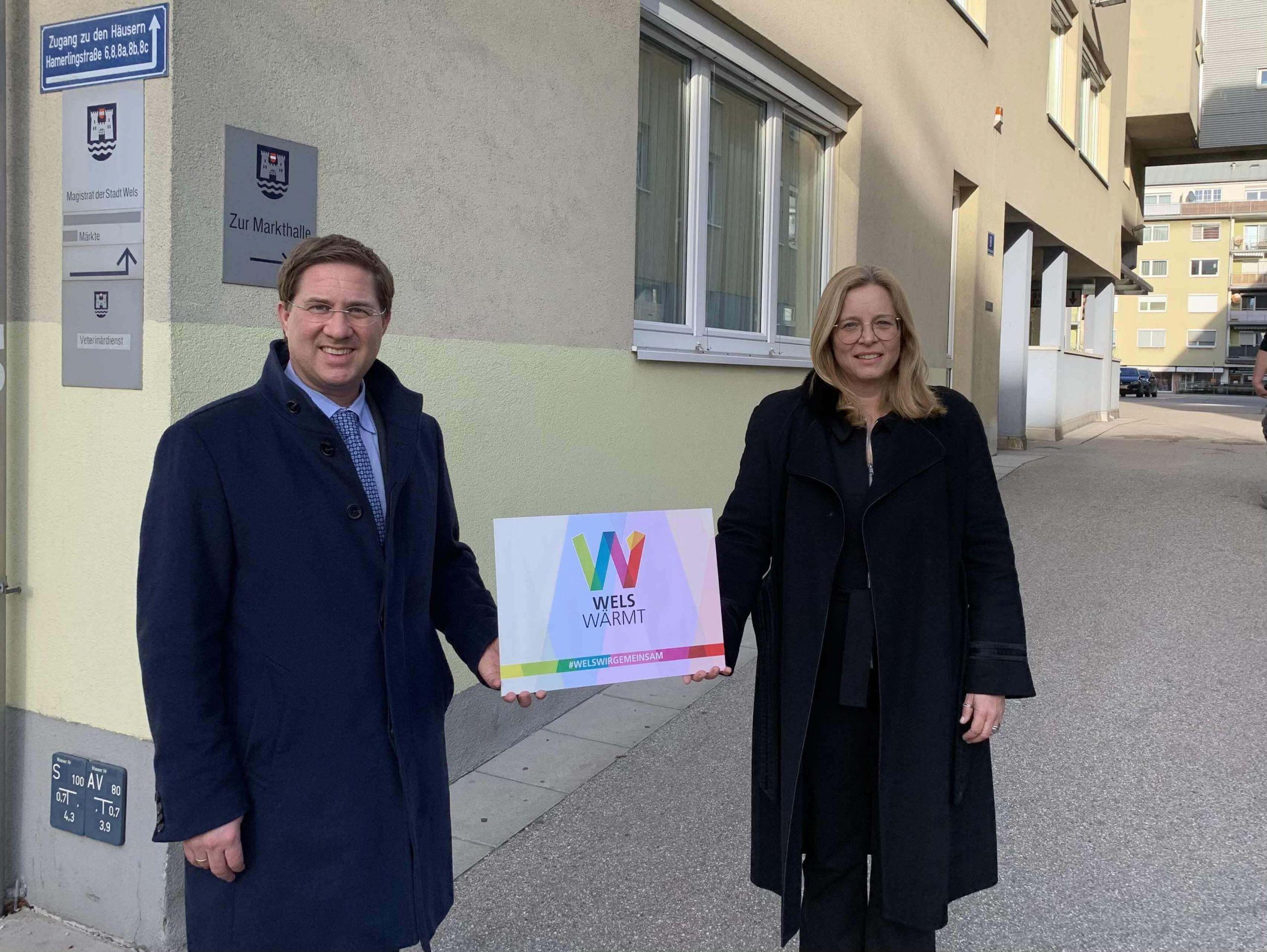 Bürgermeister Dr. Andreas Rabl und Vizebürgermeisterin Christa Raggl-Mühlberger stehen am Marktgelände und halten ein Schild mit der Aufschrift: Wels wärmt