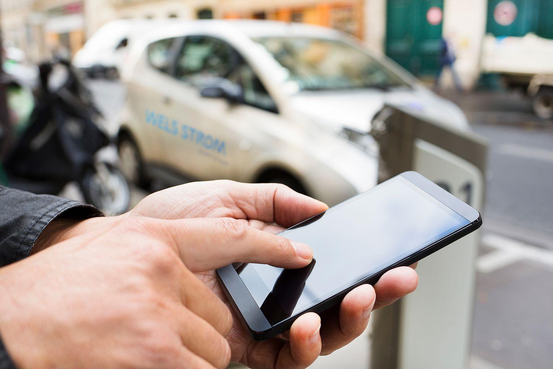 Eine Hand die auf ein Handy tippt und im Hintergrund ist ein E-Auto