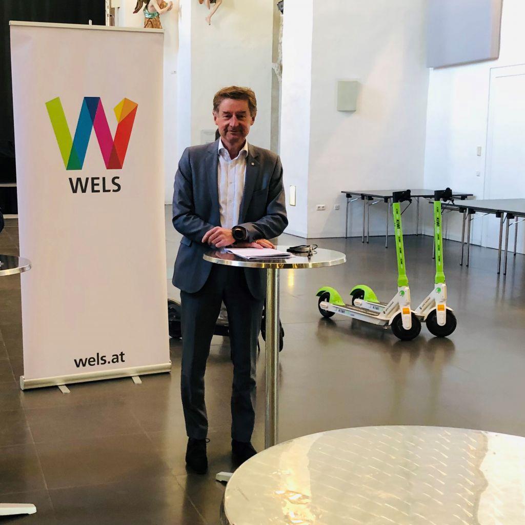 Gerhard Kroiß bei der Pressekonferenz. Er steht an einem Stehtisch. Im Hintergrund ein