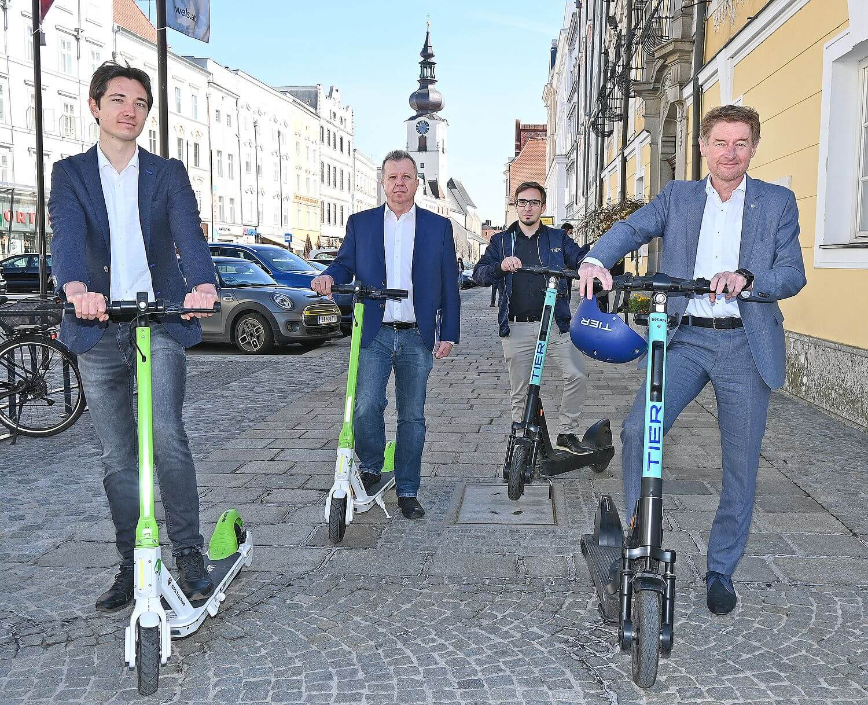 vizebürgermeister Gerhard Kroiß steht gemeinsam mit zwei Scooter Anbietern und dem Verkehrsstadtrat der Stadt Wels vor dem Rathaus. Alle Personen stehen auf einem E-Scooter