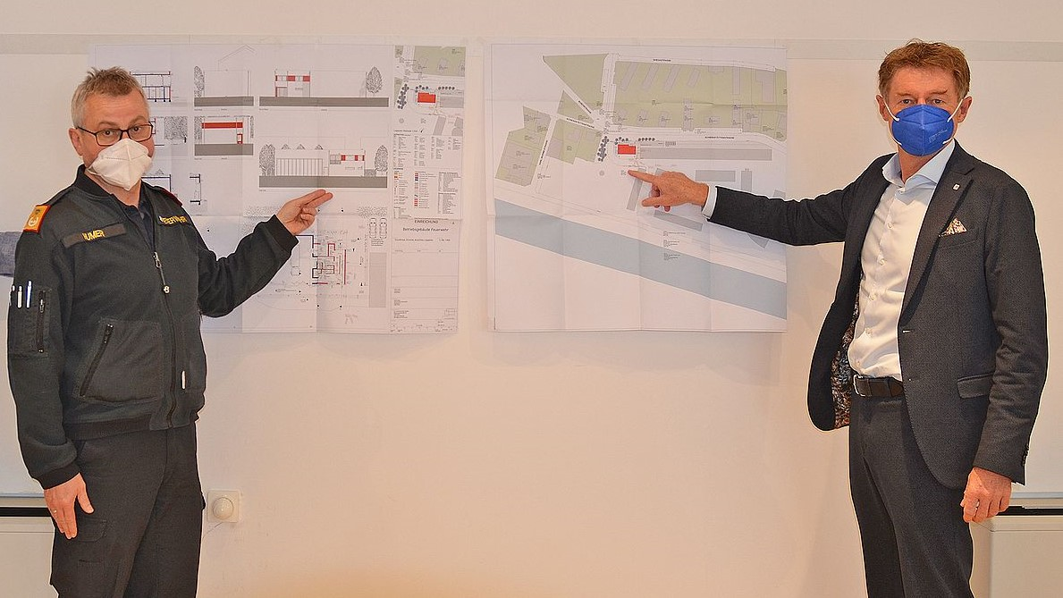 Vizebürgermeister Gerhard Kroiß und Feuerwehrkommandant Humer stehen vor den Bauplänen des neuen Feuerwehrhauses Pernau