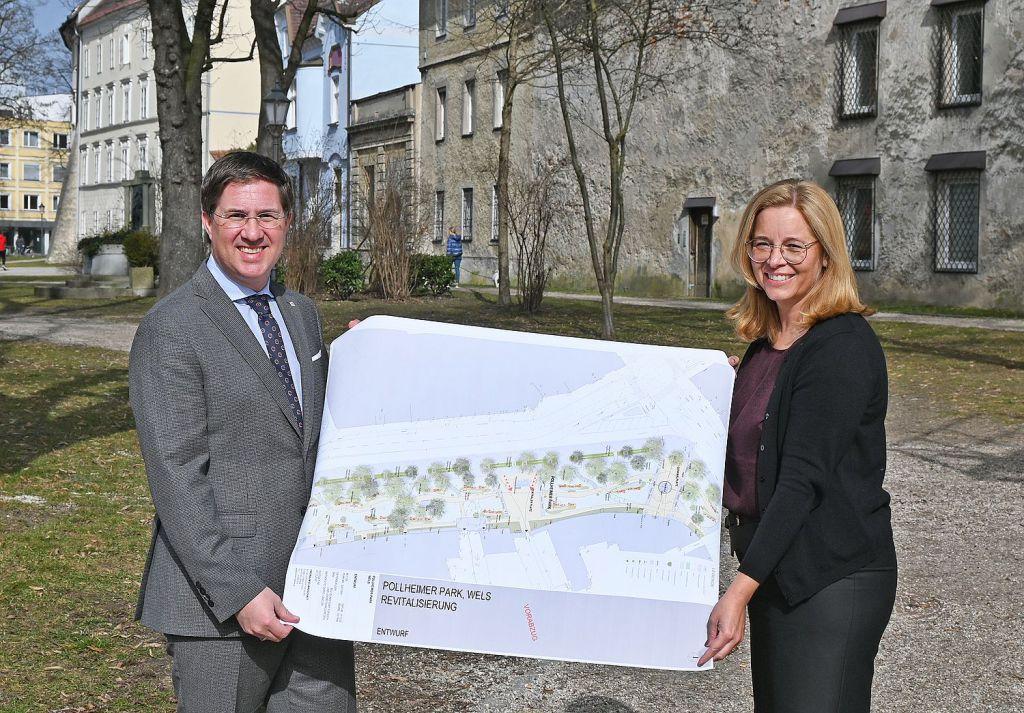 Bürgermeister Dr. Andreas Rabl und Vizebürgermeisterin Christa Raggl-Mühlberger stehen im Pollheimerpark und halten einen Übersichtsplan der Neugestaltung