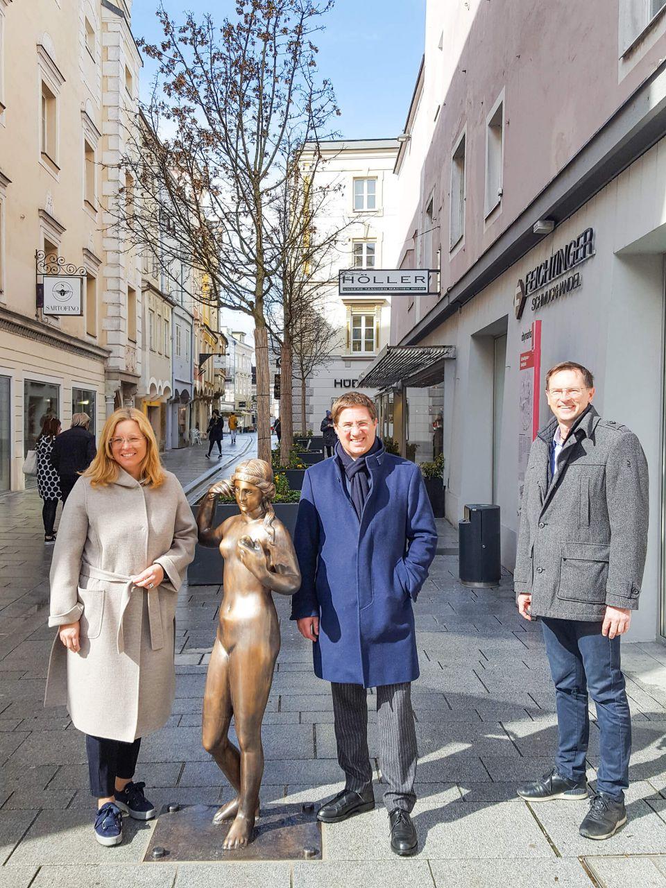 Bürgermeister Dr. Andreas Rabl, Vizebürgermeisterin Christa Raggl-Mühlberger und Robert Reif, Regionaldirektor Sparkasse Wels stehen in der Schmidtgasse neben der neuen Bronzestatue der Venus