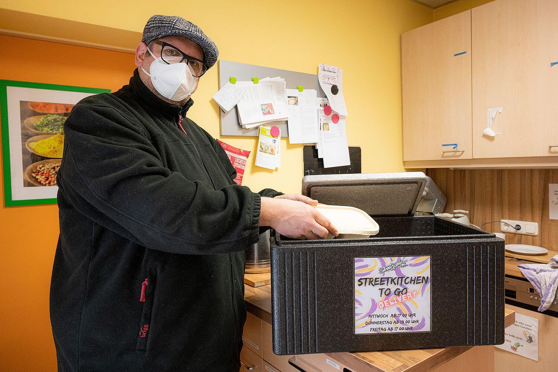 ein Streetwork-Mitarbeiter gibt Essen in die Auslieferbox der