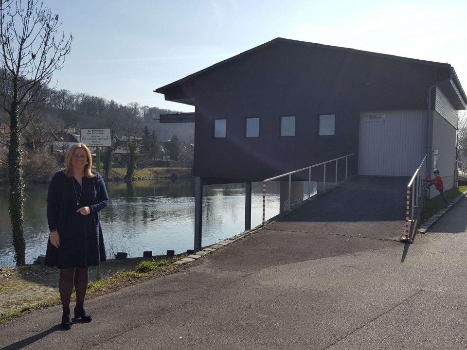 Frau Vizebürgermeister Raggl-Mühlberger steht vor dem Feuerwehrbootshaus an der Traun