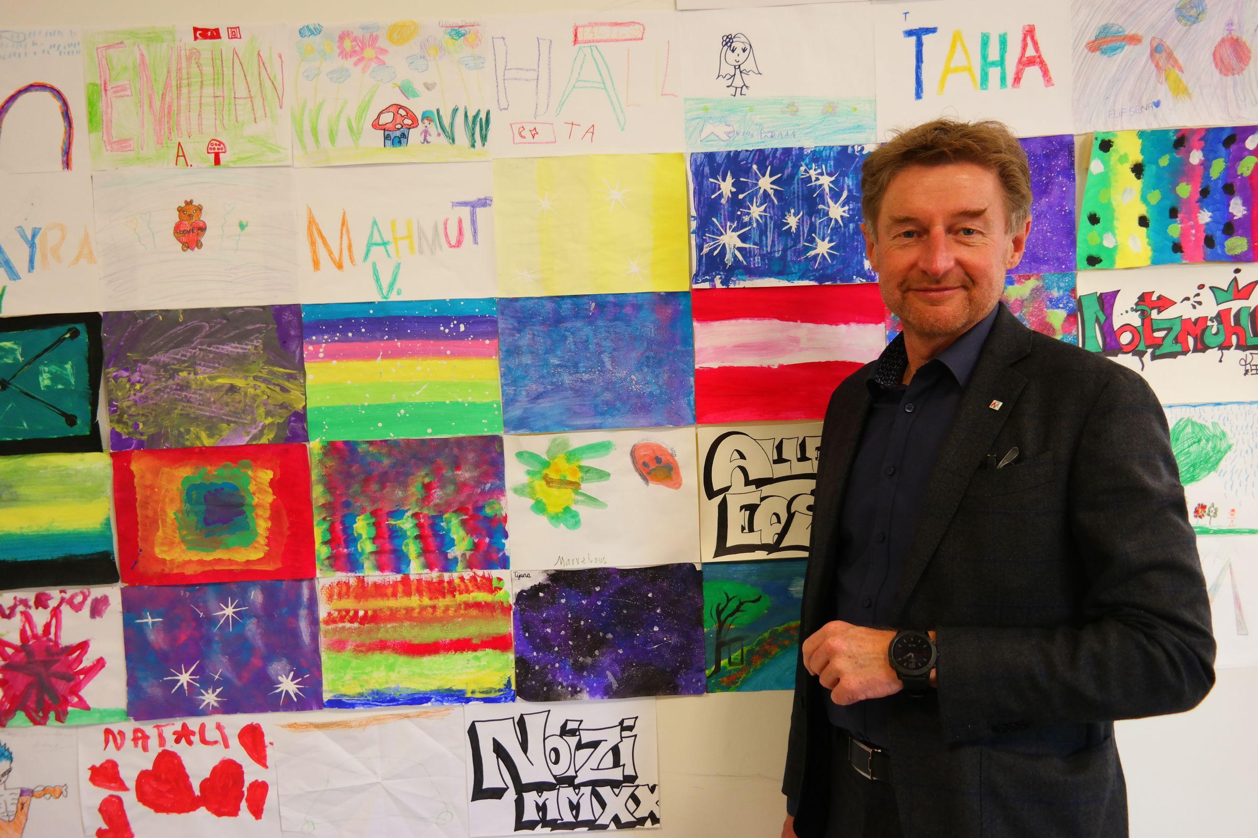 Gerhard Kroiß vor einer Wand voller Zeichnung von Jugendlichen die das Jugendtreff Noitzmühle ziehren
