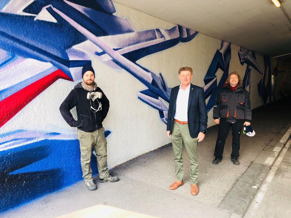 Gerhard Kroiß mit den beiden Künstlern vor der neuen Grafitti Wand der Unterführung Neustadt in Wels