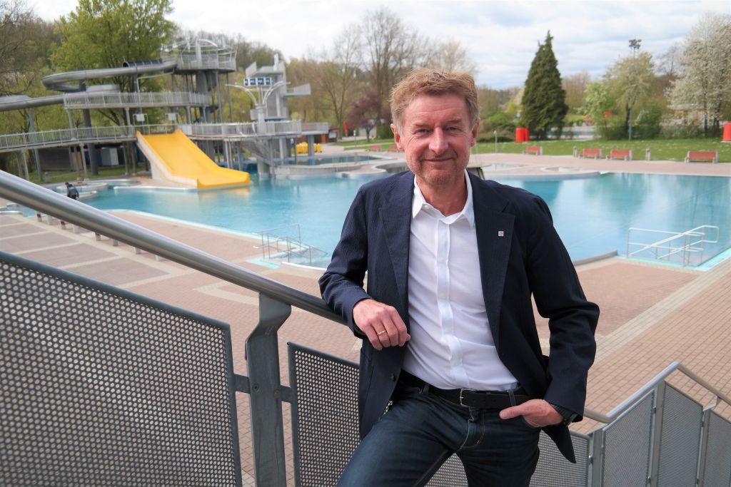 Vzbgm. Gerhard Kroiß steht auf den Treppen zum Abgang in das Welser Freibad. Im Hintergrund das Familienschwimmbecken und die Rutsche
