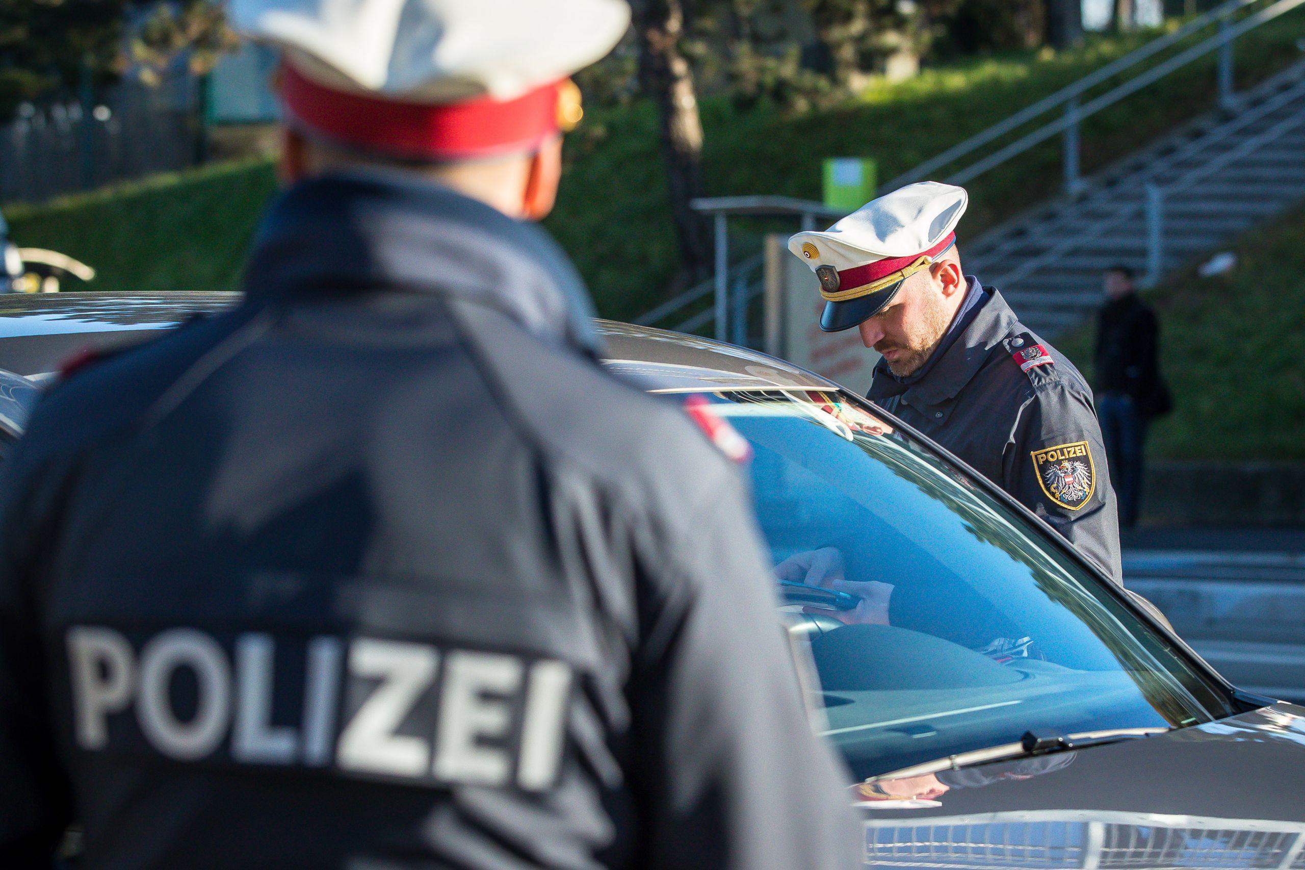 Polizist bei Kontrolle, schwarzes Auto