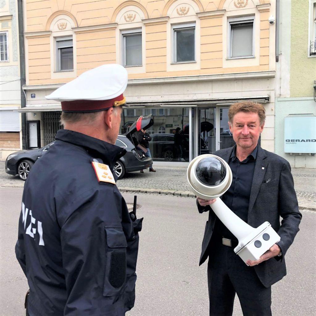 Sicherheitsreferent Vzbgm. Gerhard Kroiß hält eine Videoüberwachungskamera , neben ihm steht ein Polizist
