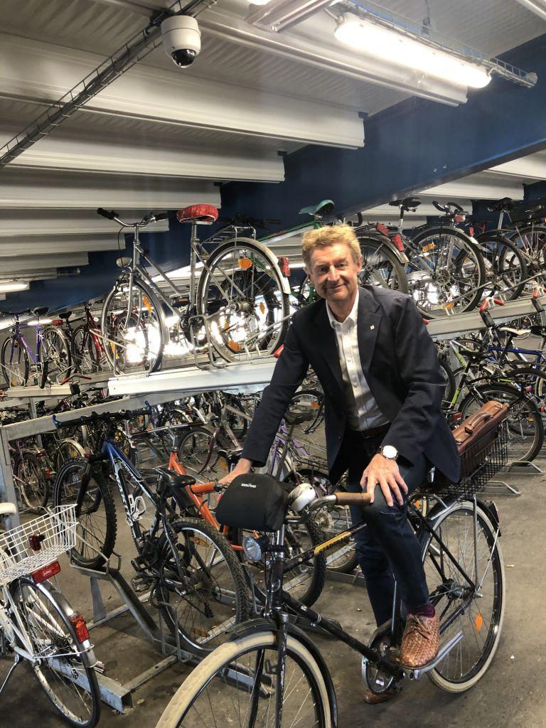 vzbgm. Gerhard Kroiß sitz auf seinem Fahrrad in der Fahrrad-Parkgarage am Welser ÖBB Parkdeck. Über ihm zu sehen ist die neue Videoüberwachung
