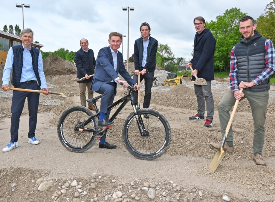 Referent Gerhard Kroiß sitz auf einem Fahrrad, hinter ihm stehen die Mitarbeiter der Dienststelle, der Baufirma mit Spaten auf der Baustelle des neuen Geländes der Pumptrack-Anlage