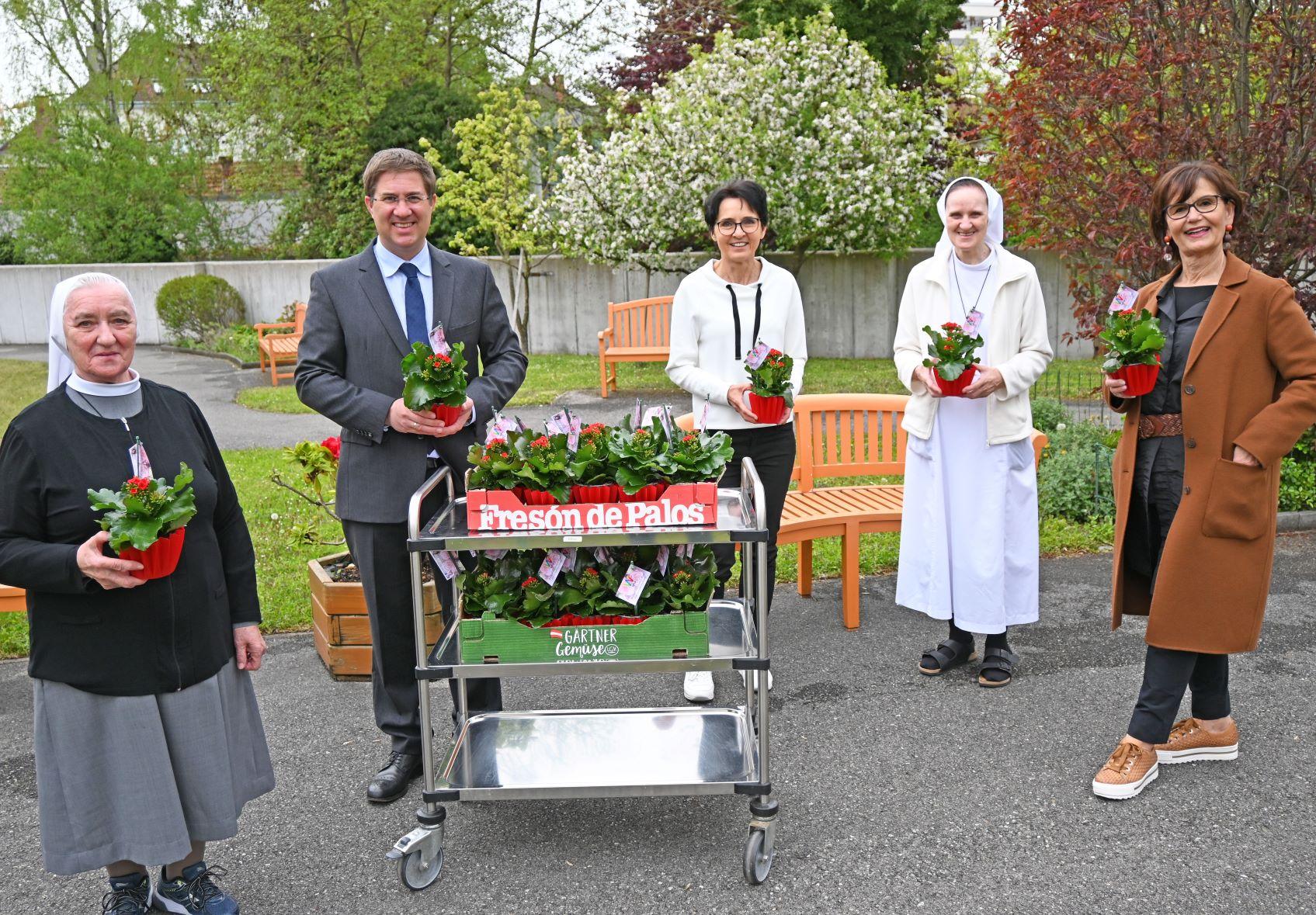 Bürgermeister Dr. Andreas Rabl und Stadträtin Josseck-Herdt übergeben die Blumenstöcke an die Bruderliebe