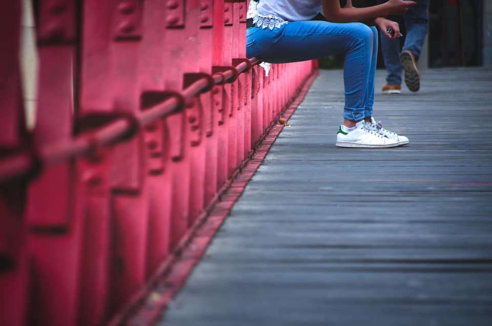 Man sieht eine Frau auf einer Brücke sitzen, das Bild endet am Oberkörper.