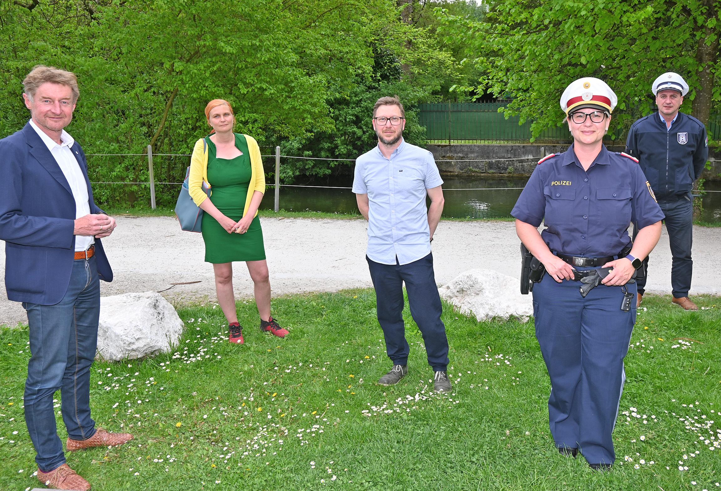 Vizebürgermeister Gerhard Kroiß steht mit den Vertretern der Polizei, der Ordnungswache und der Volkshilfe mit Abstand auf einer Wiese am Welser Zwinger