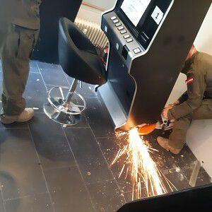 Die Cobra-Einsatzkräfte schneiden mit einer Flex einen am Boden festgeschraubten Spielautomaten los.
