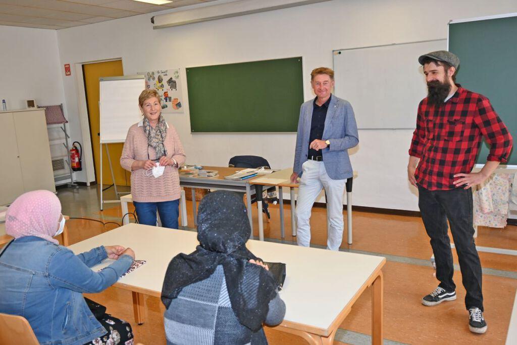 Vizebürgermeister und Integrationsreferent Gerhard Kroiß steht mit der Trainerin und einem Mitarbeiter der Volkshilfe im Unterrichtsraum, vor Ihnen sitzen 2 Kursteilnehmerinnen