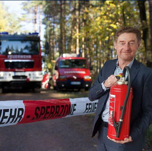 Sicherheitsreferent Vzbgm. Gerhard Kroiß mit einem Feuerlöscher in der Hand. Im Hintergrund ein Feuerwehrauto im Wald