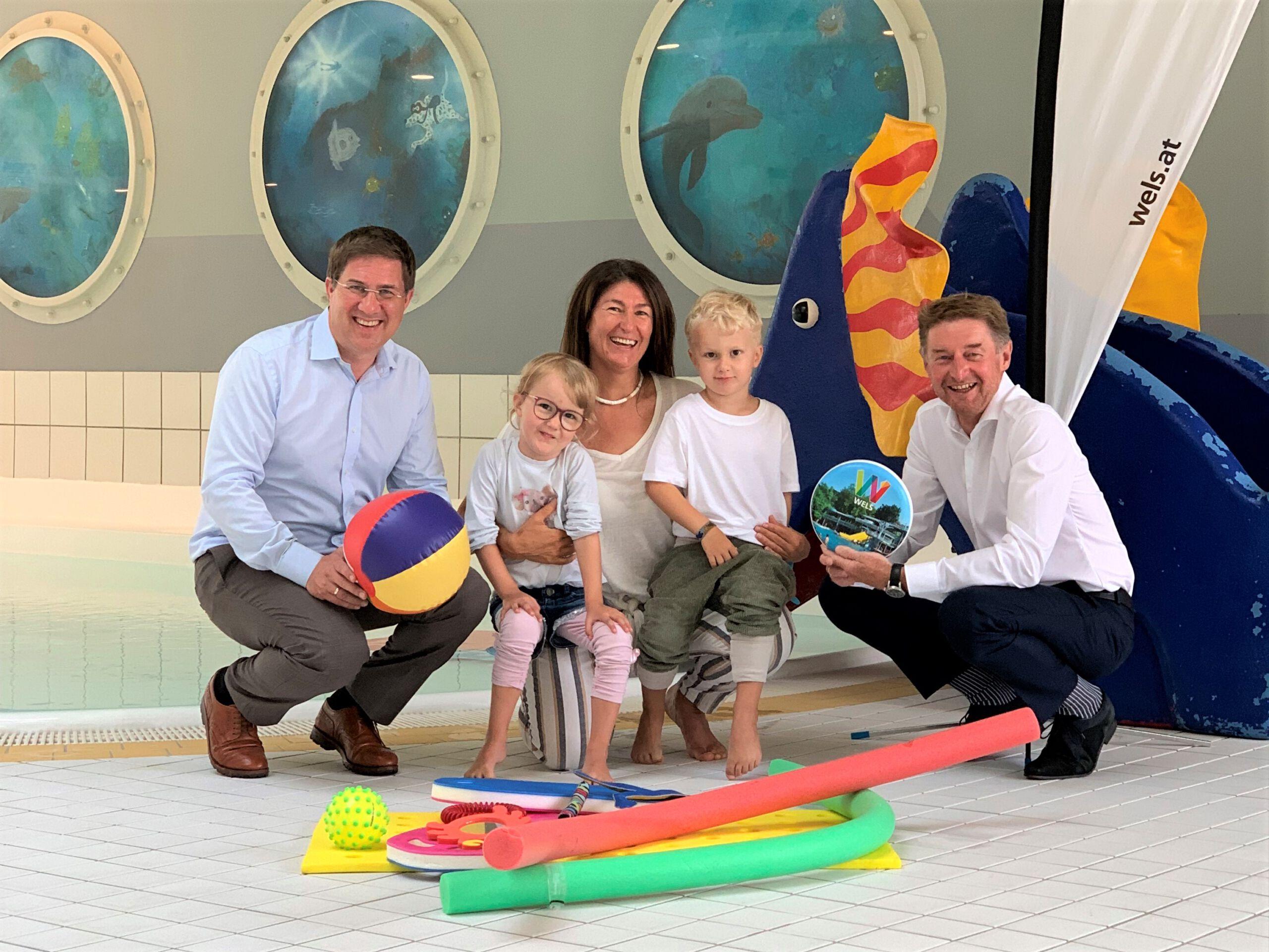 Bürgermeister Dr. Andreas Rabl und Sportreferent Vzbgm. Gerhard Kroiß mit der Schwimmtrainerin und 2 Kindern vor dem Schwimmbecken im Welser Hallenbad