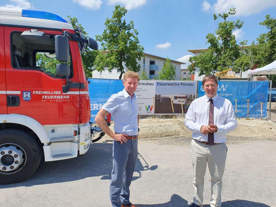 Bgm. Dr. Andreas Rabl und Vzbgm. Gerhard Kroiß stehen neben einem Feuerwehrfahrzeug neben der Stelle, wo der Spatenstich stattgefunden hat.
