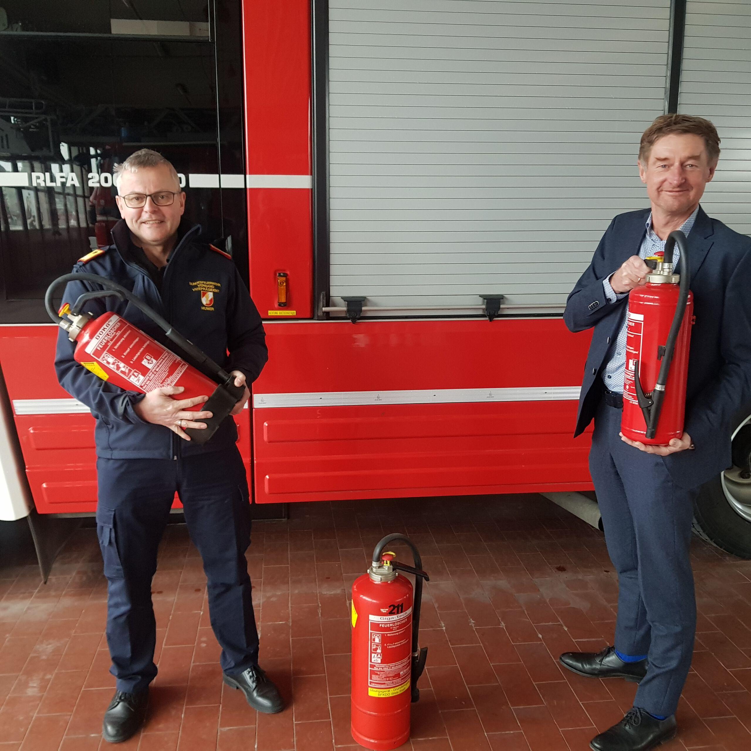 Feuerwehrkommandant Ing. Humer und Vzbgm. Gerhard Kroiß mit Feuerlöschern in der Hand vor einem Feuerwherauto