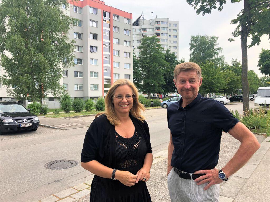 Vzbgm. Gerhard Kroiß und Vzbgm. Christa Raggl-Mühlberger stehen vor Hochhäusern in der Noitzmühle