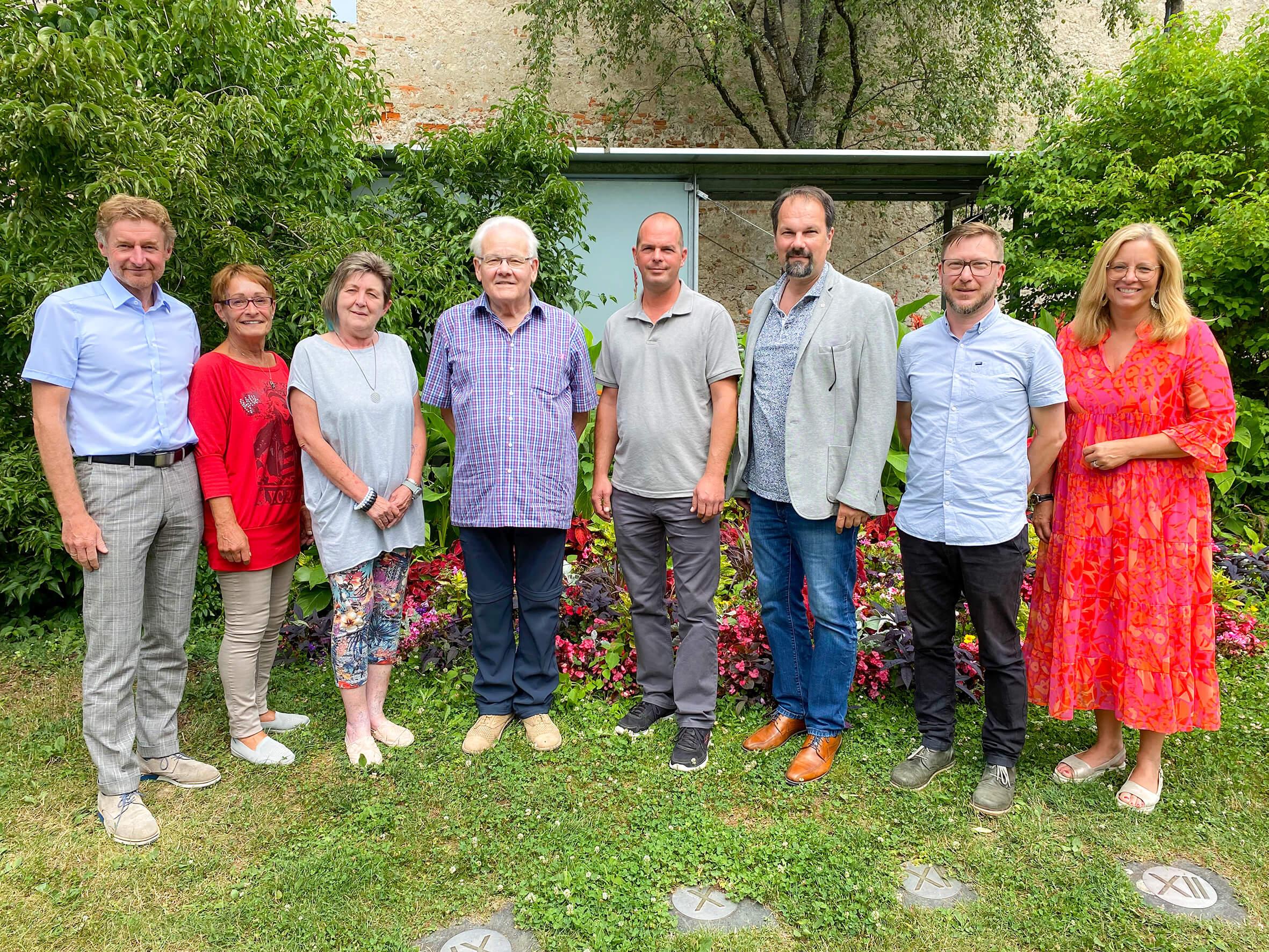 Die beiden Referenten stehen gemeinsam mit den Nachbarschaftssprechern und den Mitarbeitern von Wohnen im Dialog und der Welser Heimstätte auf einer Wiese