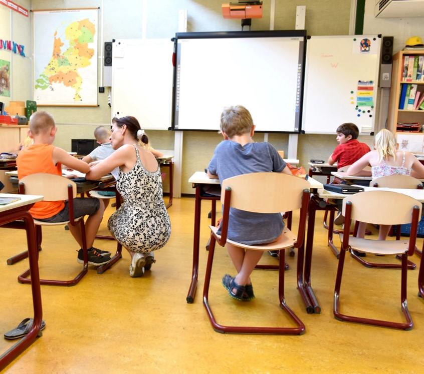 Lehrerin kniet bei einem Schüler , die Kinder sind von Hinten auf den Schulbänken zu sehen