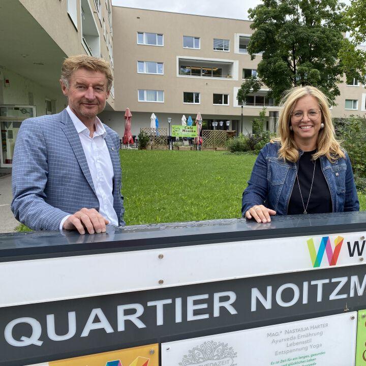 Herr Vizebürgermeister Kroiß und Frau Vizebürgermeister Raggl-Mühlberger stehen in der Noitzmühle hinter dem Schild