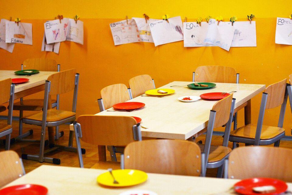 Schulklasse mit Teller auf den Tischen