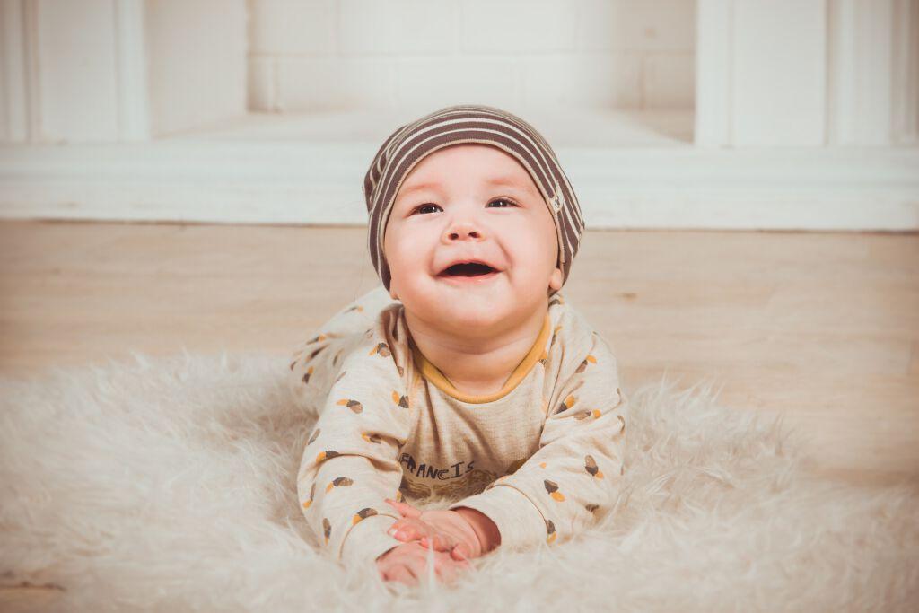 lachendes Baby liegt auf einem Fell am Boden
