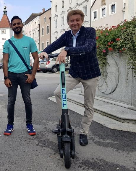 Herr Vizebürgermeister Kroiß steht mit einem E-Scooter und einem Mitarbeiter der Firma Tier neben dem Brunnen vor dem Rathaus mit Blick auf den Ledererturm