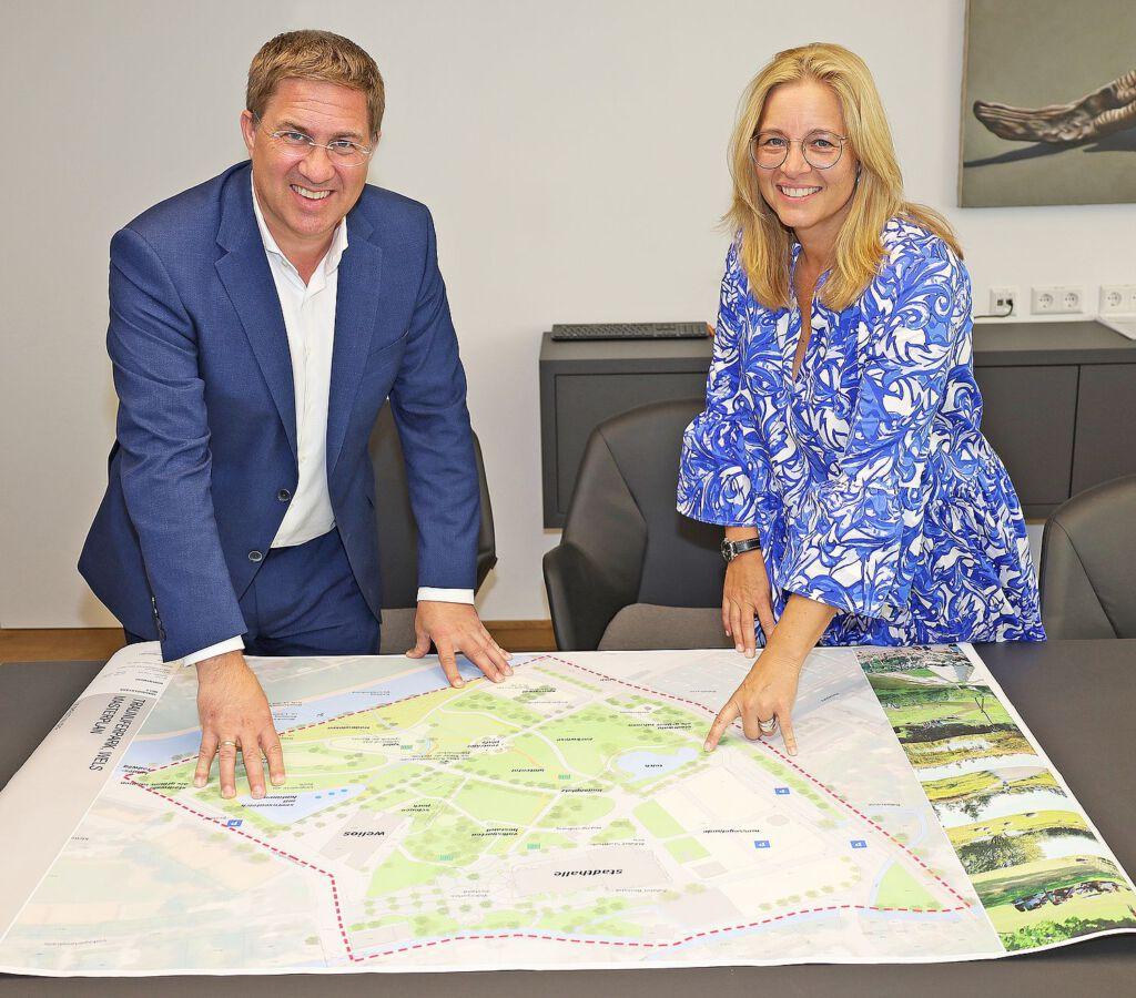 Bürgermeister Dr. Andreas Rabl und Vizebürgermeisterin Christa Raggl-Mühlberger stehen vor dem Plan des zukünftigen Central Parks