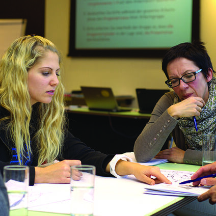 mehrere Personen sitzen an einem Tisch und lernen