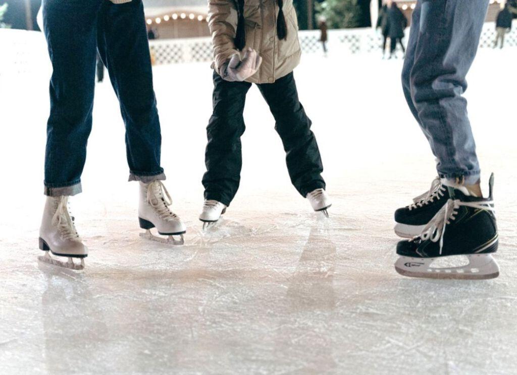 Man sieht drei Paar beine mit Schlittschuhen auf der Eisfläche